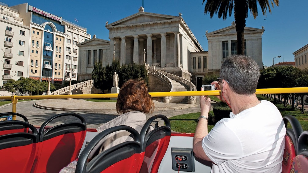 bus passengers taking pictures of historical buildings in Athens