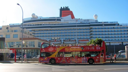 red double decked bus picking up passengers near a large cruise ship in Cadiz