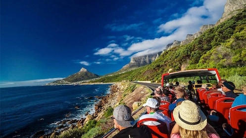 Tourists enjoying a view of the coast from a hop-on hop-off bus in Cape Town