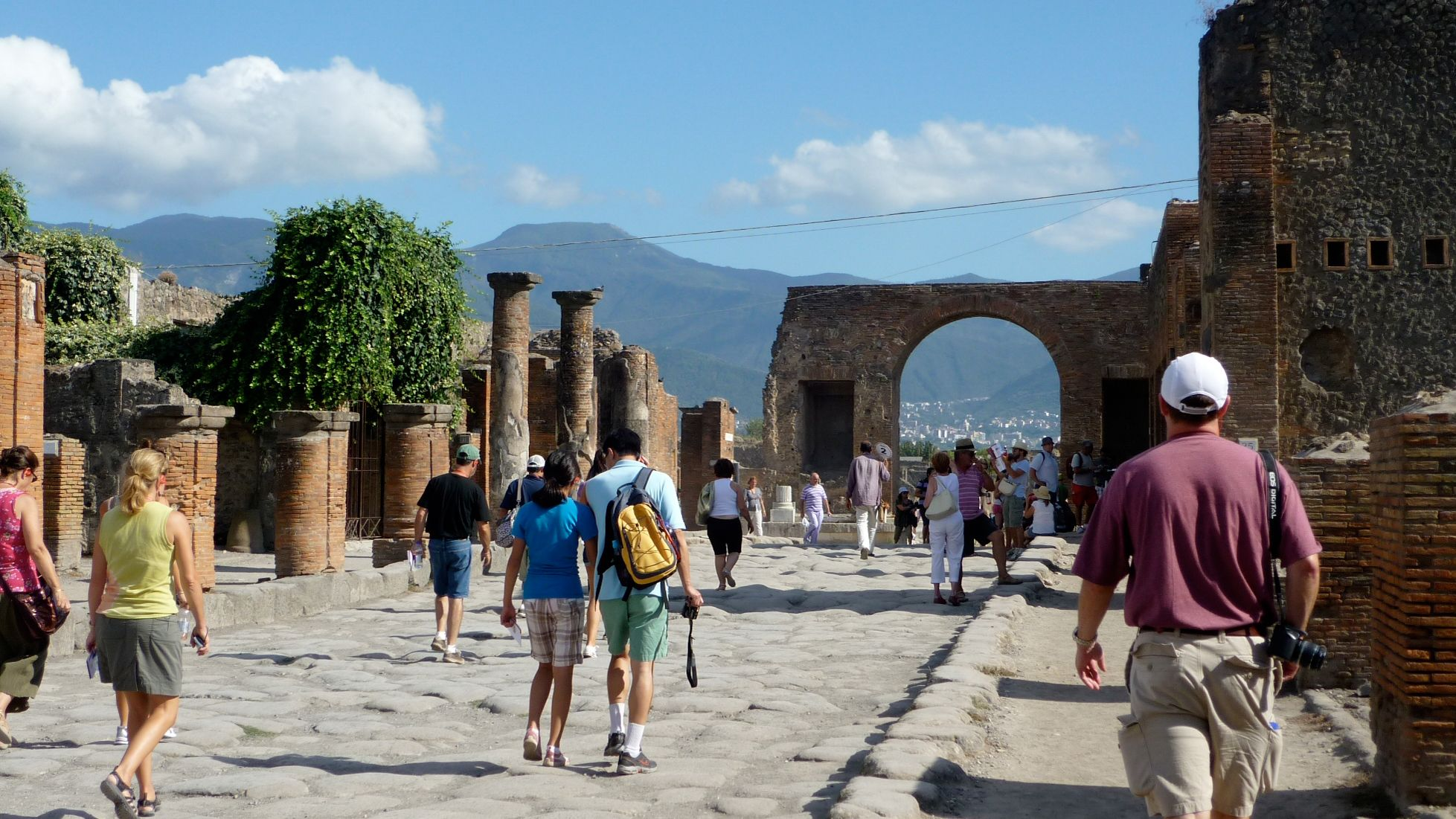 Several tourists walking about in Pompeii preservation site.