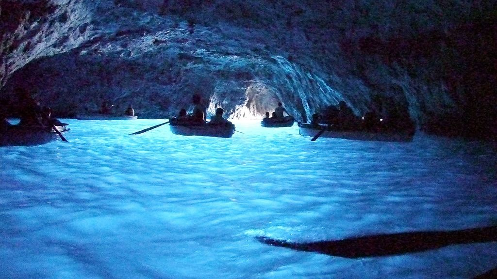 People passing through coastal cave in Italy