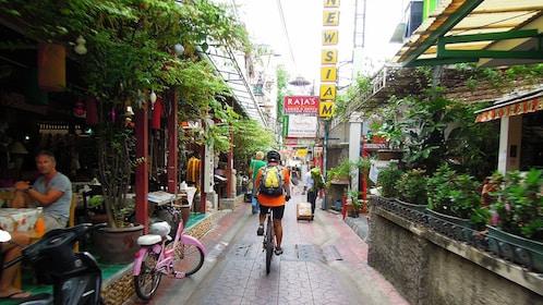 riding bike through the wet street pavement in Bangkok