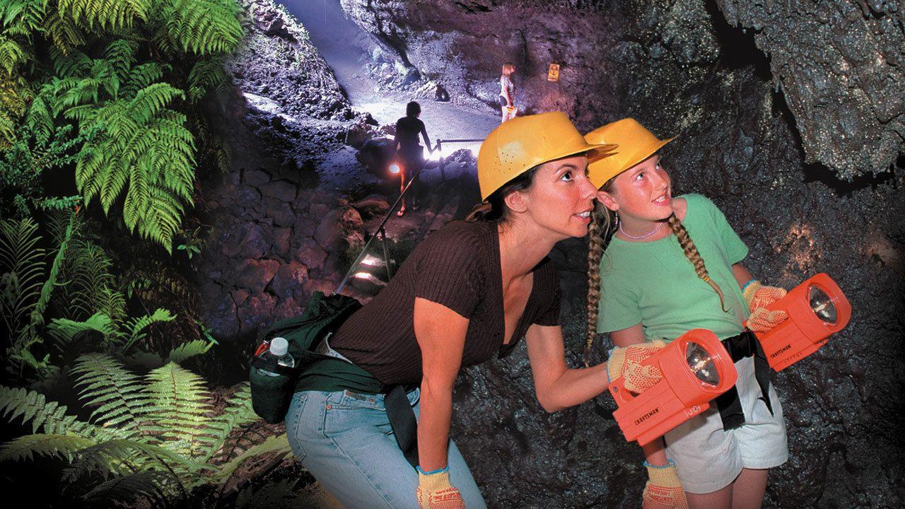 Mother and daughter with flash lights in cave in Maui