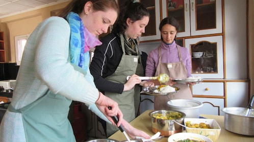 Three women doing various tasks in a Nepalese cooking class