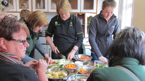 Seven people doing various tasks in a Nepalese cooking class Source: Supplier Provided