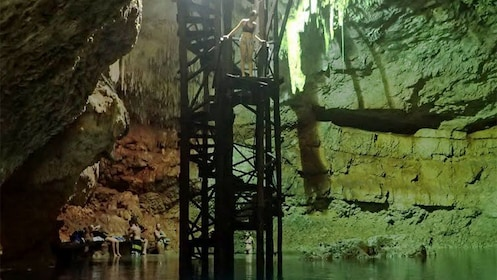 Woman on a platform about the jump in the water in a cave in Mexico