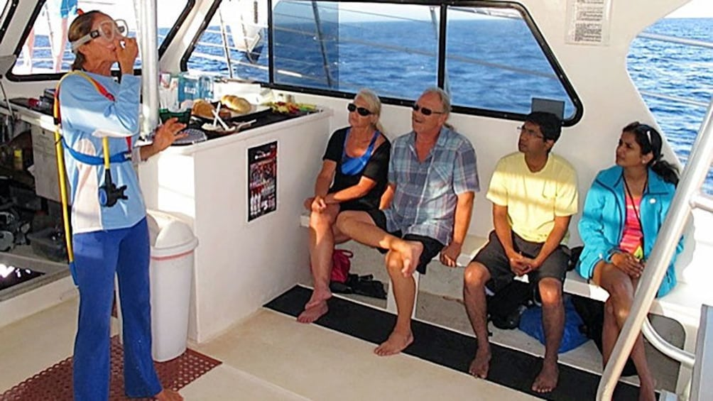 Show item 10 of 10. Snorkel instructor demonstrating on a boat in Maui