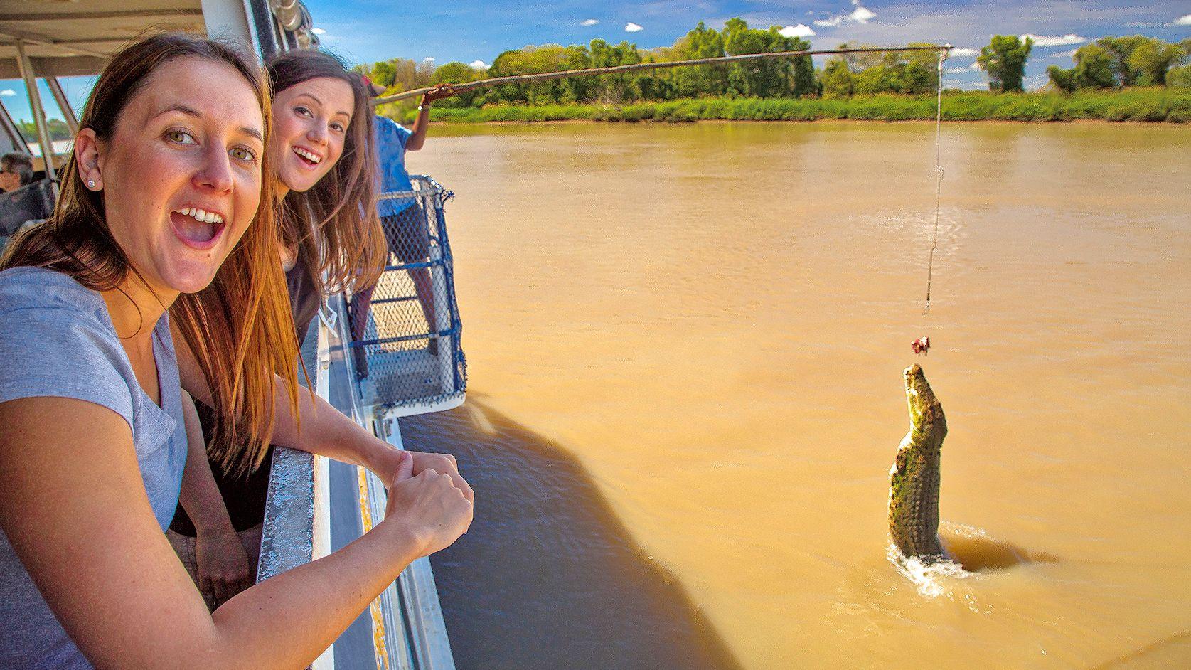 girls watching alligator jumping