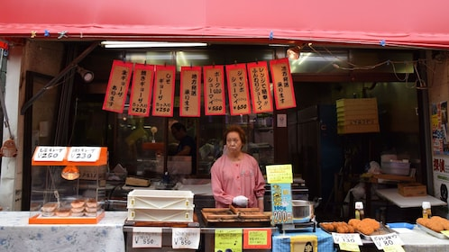 woman standing behind a food booth in Japan