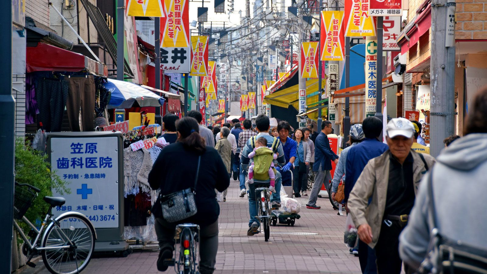 pedestrians and bikers on a crowded street in Japan