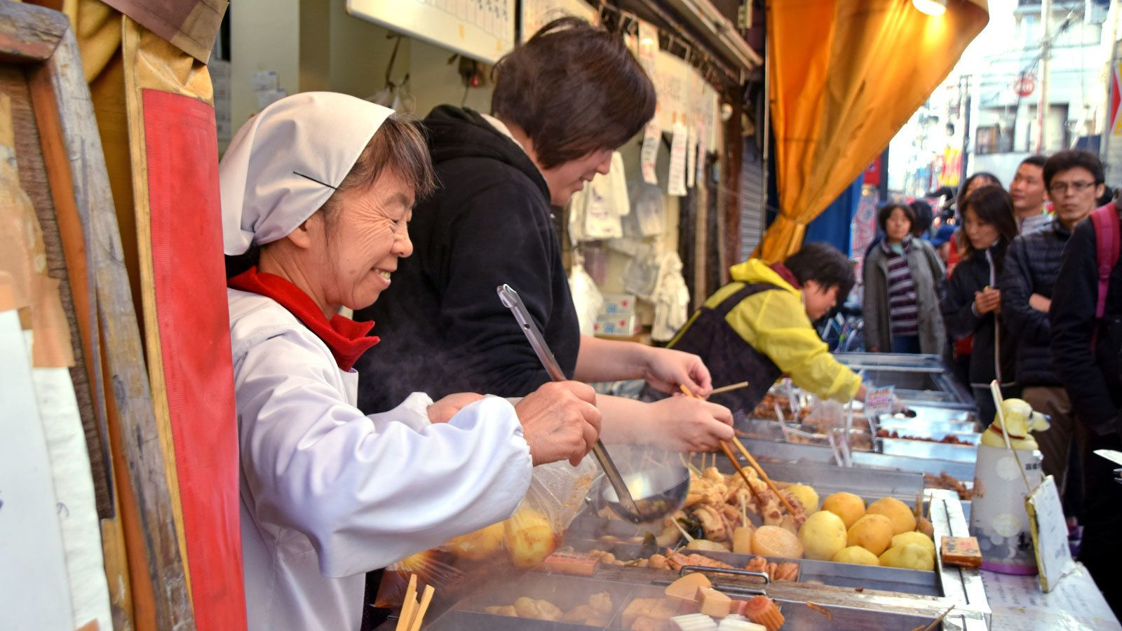 serving food at a busy street market in Japan