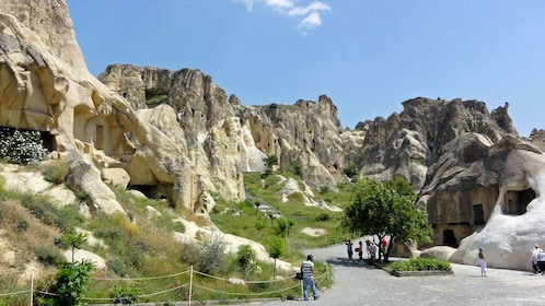 People walking past dwellings and rock formations in Cappadocia