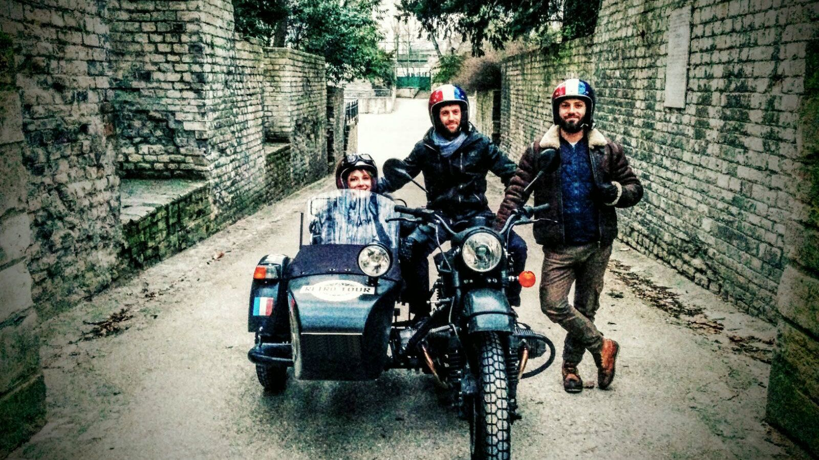 Group with a motorcycle and sidecar on a narrow street in Paris