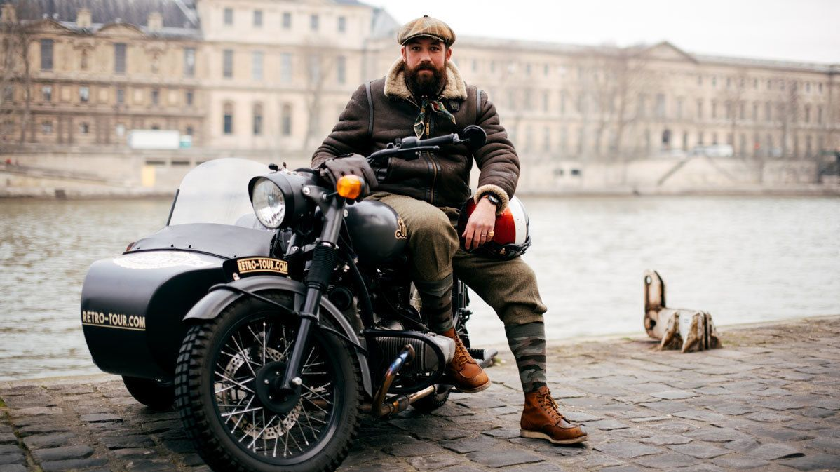Man on a motorcycle with sidecar along the Seine River in Paris