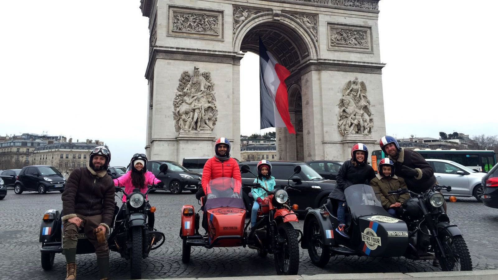Group on motorcycles with sidecars in front of the Arc de Triomphe in Paris