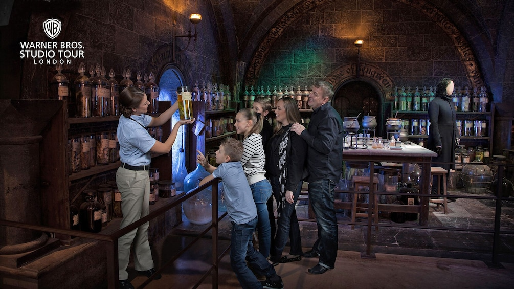 Show item 9 of 9.  A tour guide takes a group through Snape's potion class in the Wizarding World of Harry Potter