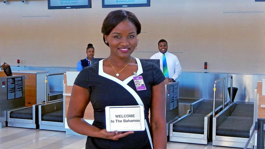 Show item 1 of 5. woman with a welcome sign at the airport in Nassau