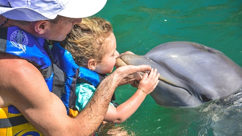 Young girl kissing dolphin, with guidance from father.