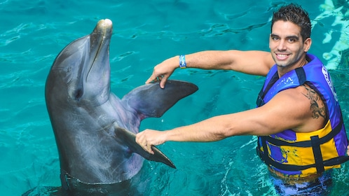 Young man interacting with dolphin in water.