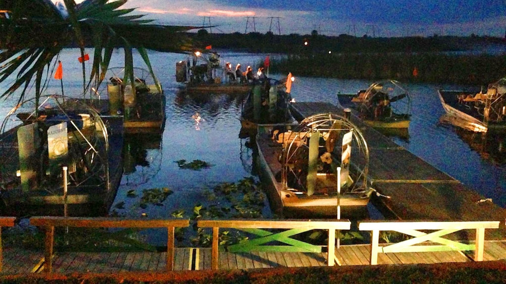 Show item 2 of 9. Airboats tied up at docks at dusk