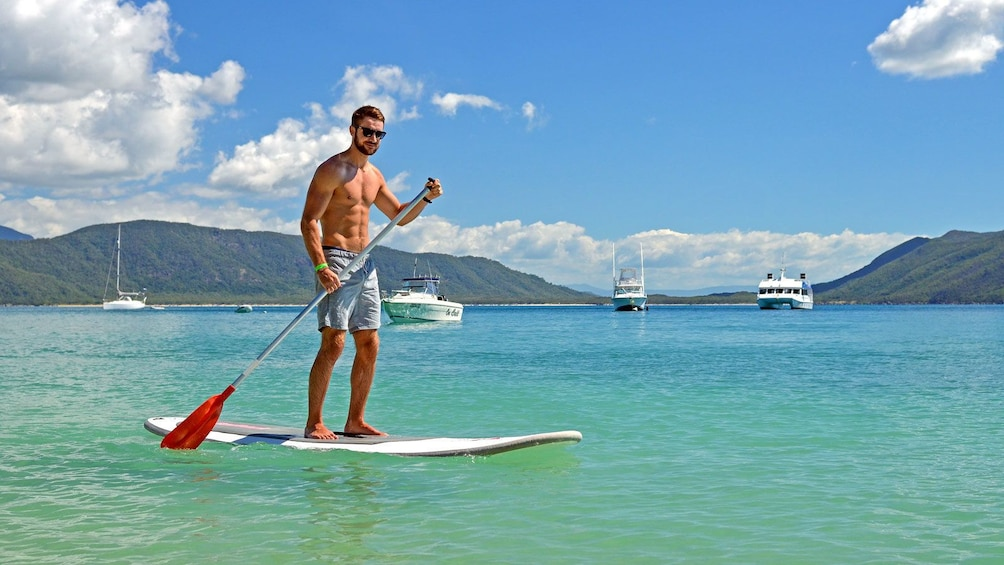 muscular man paddle boarding in Australia