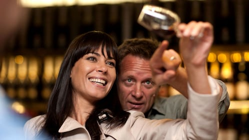 A smiling woman holds up a wine glass on its side and a man behind her points at the wine in it