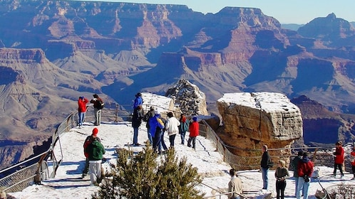 People stand at a snowy overlook at the Grand Canyon