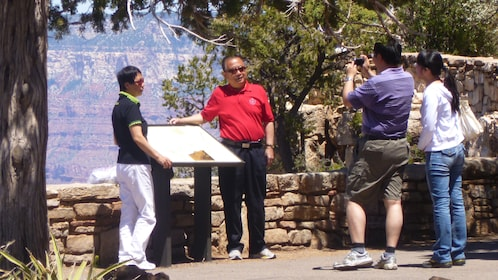 People pose at a outlook over the Grand Canyon and take pictures