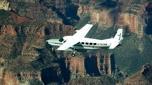 A single engine plane flying over the Grand Canyon