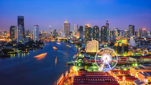 Aerial nighttime view of Bangkok with river pictured.