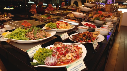 Angled view of buffet table with several traditional dishes inside cruise boat.