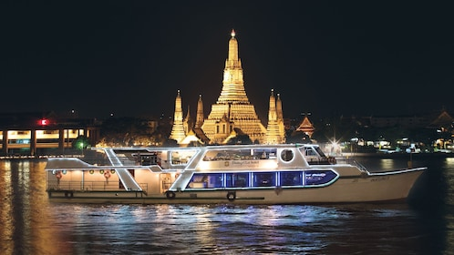 Cruise boat filled with several people shown at night with Wat Arun temple in the distance.