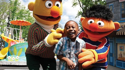 Boy laughing with costume characters in Sesame Place