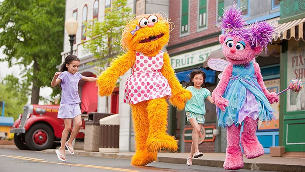 Show item 4 of 8. Girls skipping with costume characters in Sesame Place