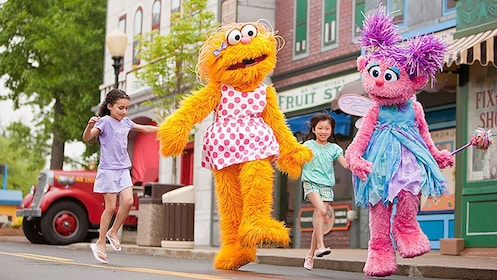 Girls skipping with costume characters in Sesame Place