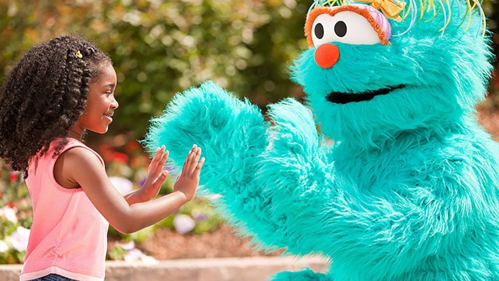Show item 3 of 8. Girl playing with costume character in Sesame Place