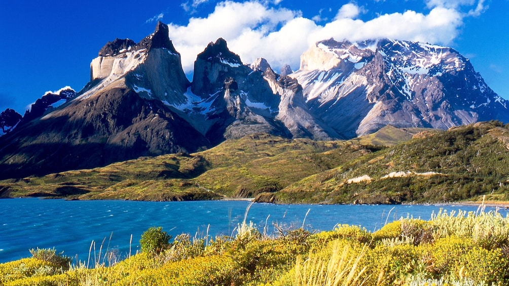 Scenic vista of snowcapped Patagonia mountain top next to crystal blue lake and green hills.