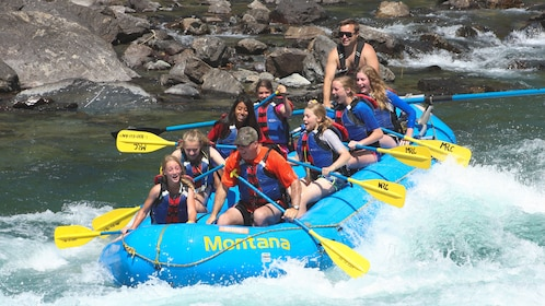 Several people on blue raft paddling down actively flowing river.