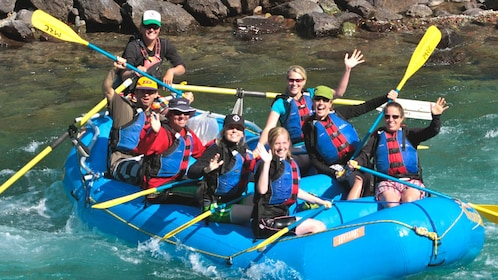 Several people on blue raft posing for camera with paddles.