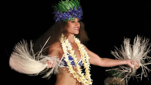 Luau performer with fans and colorful head dress