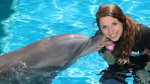 Woman getting kissed by a dolphin at the Dolphin Swim Adventure in Panama City, FL