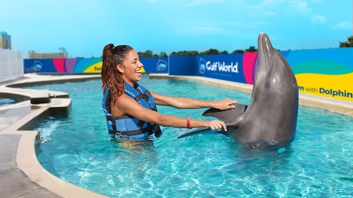 Woman holding onto dolphin's fins at Dolphin Discovery in Panama City, Florida