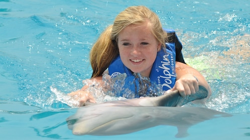 Woman swimming with a dolphin on the Dolphin Swim Adventure in Panama City, FL