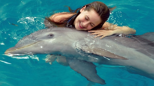 Woman hugs dolphin at Dolphin Discovery in Panama City, Florida