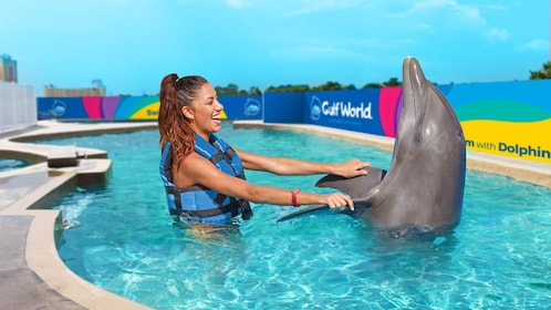 woman holding a dolphin's flippers above water in Panama City