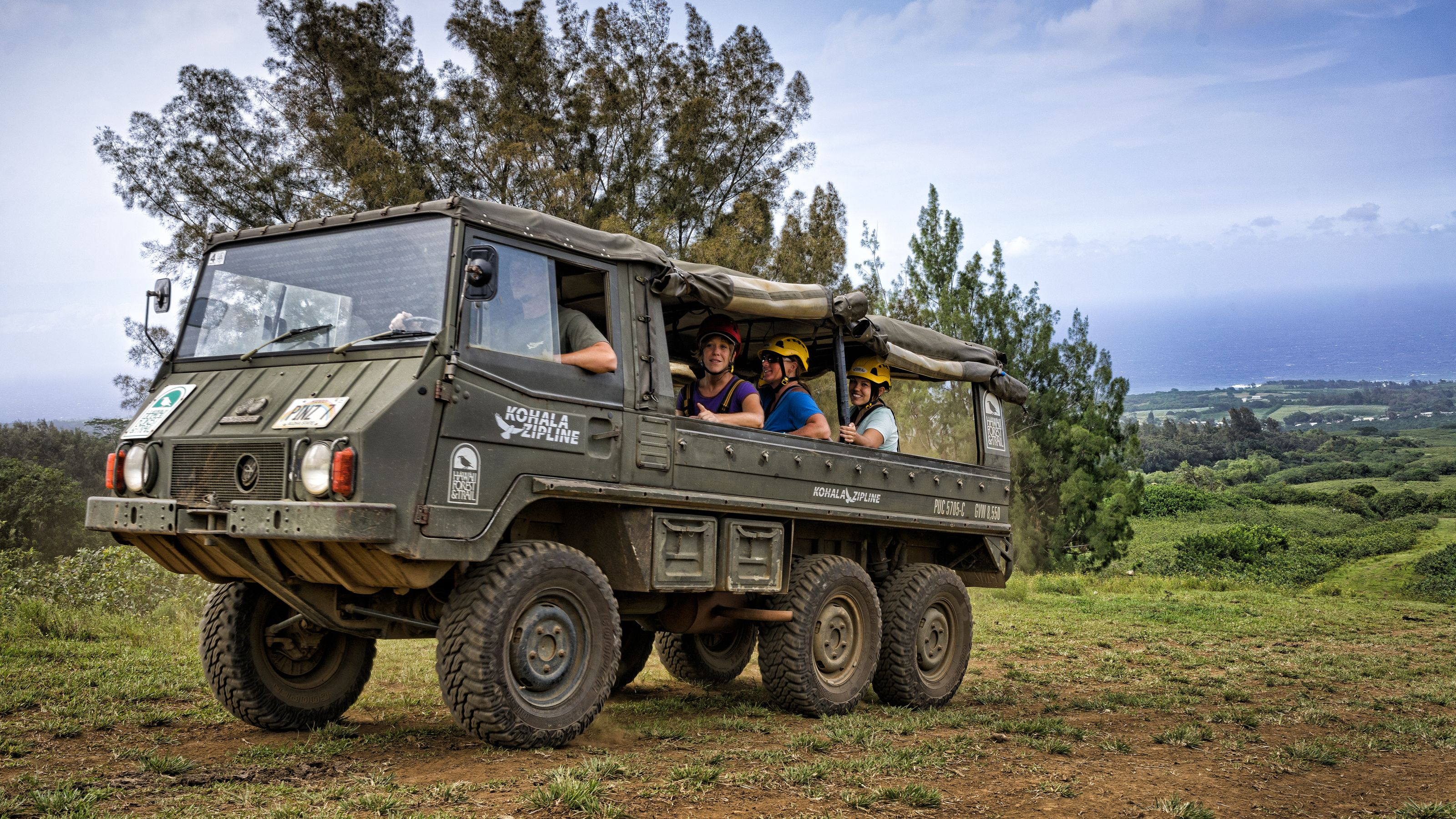 People in a truck on their way to a ziplining course in Hawaii