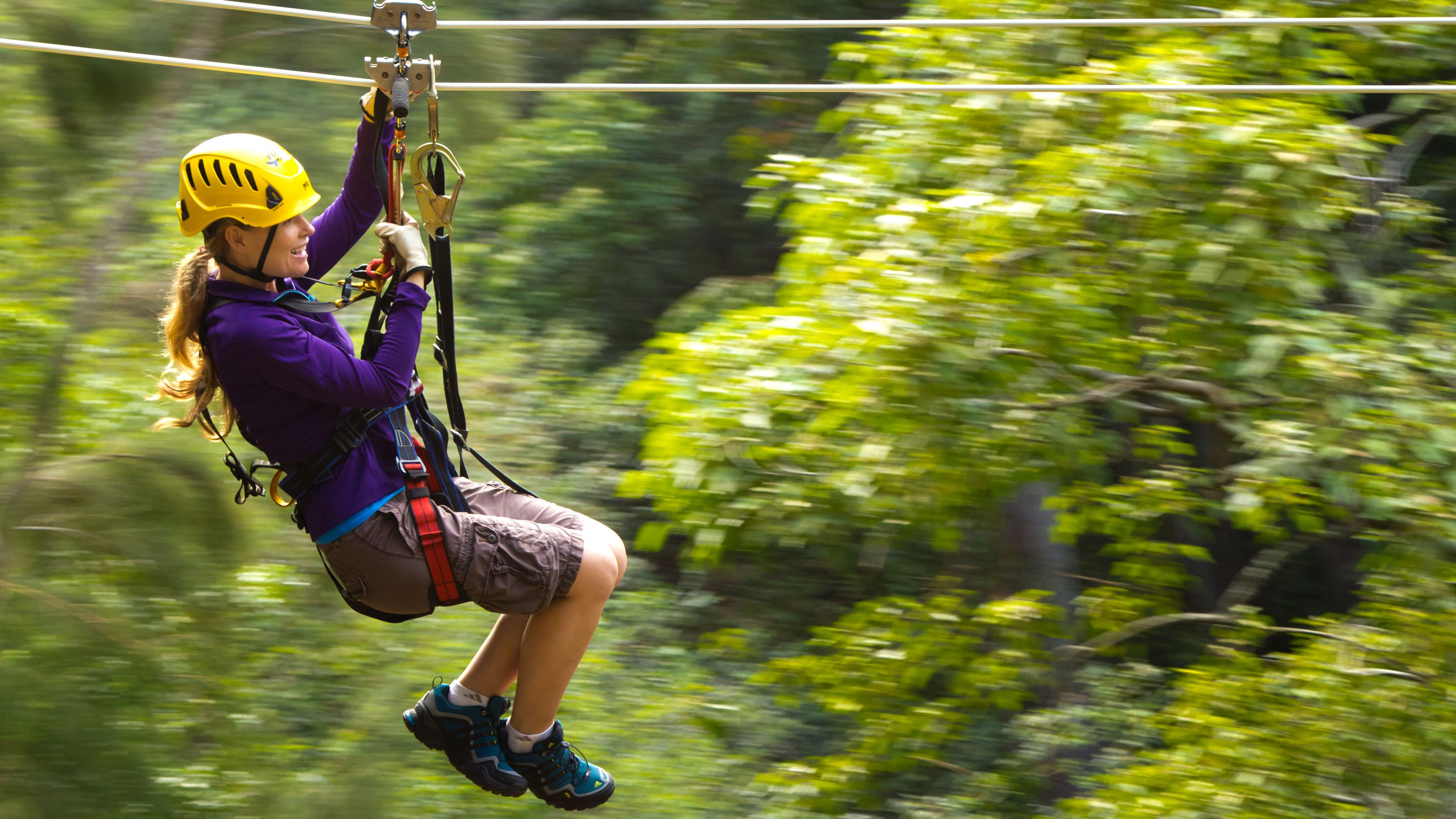 A woman ziplining through a forest in Hawaii