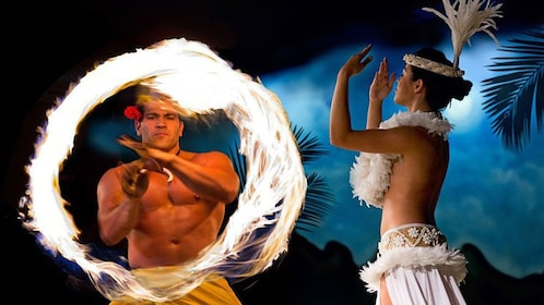 Fire spinning performer and dancer in white outfit.