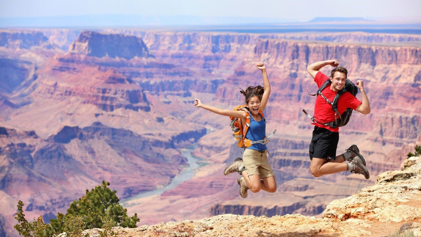 Couple jumping for joy on the edge of the Grand Canyon