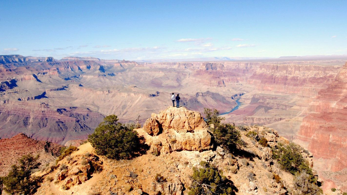 Couple standing on a rock overlooking the Grand Canyon